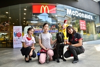 This picture shows Kirin Techawongtham, or Nong Sai, with her guide dog Luther on a visit to McDonald's Whizdom 101 recently.