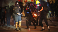 A rioter throws a gasoline bomb at police in Wan Chai. [PHOTO/CHINA DAILY]