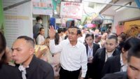 "Prime Minister Prayut Chan-o-cha, centre, was mocked by a woman during his visit to a market when she started singing a song, ""We will fulfill our promises"