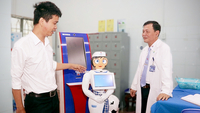 Võ Hồng Quân, director of the Centre of Information and Technology under the Eastern People Military Hospital in HCM City (left), introduces the nurse robot named Tấm. — VNA/VNS Photo Xuân Khu