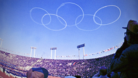 Vapor trails from jets flown by Blue Impulse, the Air Self-Defense Force's acrobatic squadron, form the Olympic logo over the old National Stadium at the 1964 Tokyo Games. MUST CREDIT: Japan News-Yomiuri file photo