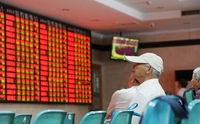 An investor checks share prices at a securities brokerage in Nanjing, capital of Jiangsu province. [Photo provided to China Daily]