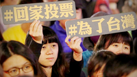 "Two supporters hold signs that read ""go home to vote"" and ""for Taiwan"" at a rally in Taipei on Thursday. (CNA)"