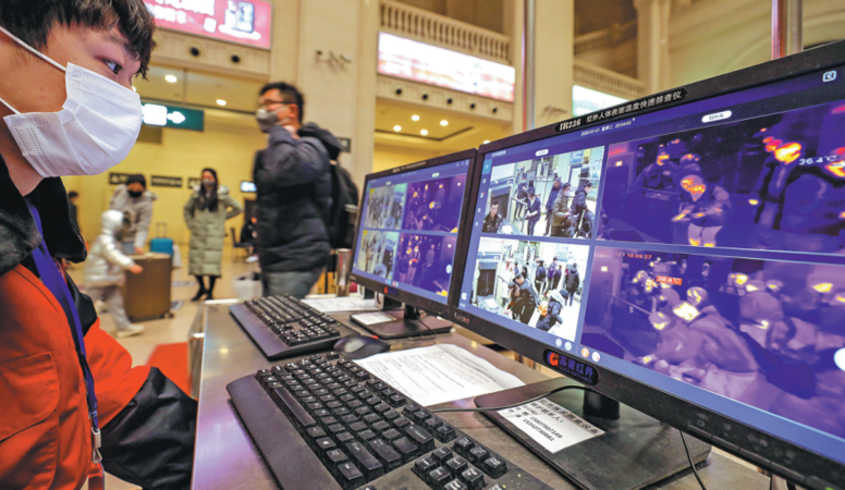 An employee of Hankou Railway Station in Wuhan, Hubei province, identifies a passenger with fever, on a computer screen showing the person's body temperature as 38.4 C. Travelers with fever at the train station are asked to register and are provided with medical assistance. YUAN ZHENG/FOR CHINA DAILY