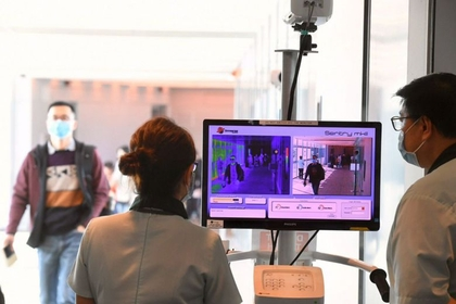Passengers arriving at Changi Airport Terminal 3 from a Hangzhou flight go past a thermal scanner.ST PHOTO: DESMOND FOO
