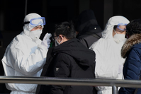 Travelers are checked by health personnel at the entrance to an underground train station in Beijing on Jan. 24. Security and health officers are working to prevent the spread of a deadly SARS-like virus that originated in Wuhan. China has sealed off millions living near the epicenter of the outbreak. (AFP/Noel Celis)