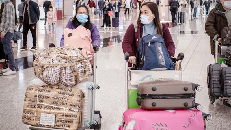 Passengers wear surgical masks at the check-in terminal at the Hong Kong International Airport in Hong Kong on Jan. 30, 2020. MUST CREDIT: Bloomberg photo by Ivan Abreu.