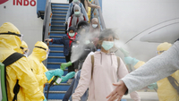 Medical officers spray disinfectant liquid on Indonesian citizens coming from Wuhan, China upon arrival at Hang Nadim Airport, Batam, Riau Islands, on Feb. 2. A total of 238 Indonesian citizens who had been in Wuhan, China were subsequently transferred to Natuna to undergo observation for approximately two weeks to ensure they were healthy and free from the coronavirus. (Antara/Handout Ministry of Foreign Affairs)
