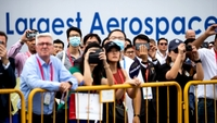 Spectators wearing protective masks look and photograph an aerobatics team performing maneuvers at the Singapore Airshow in Singapore on Feb. 11, 2020. MUST CREDIT: Bloomberg photo by SeongJoon Cho.