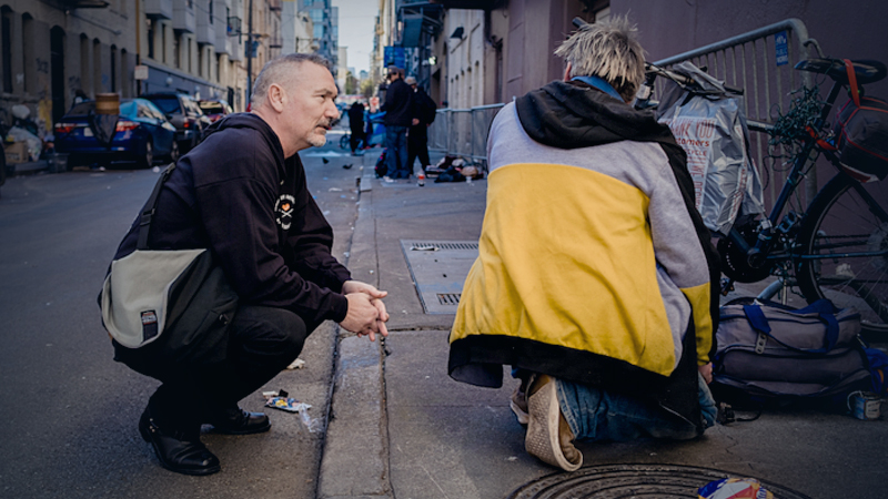 Paul Harkin, director of harm reduction at GLIDE, hands out naloxone, fentanyl detection packets and tinfoil in an alleyway in San Francisco's Tenderloin neighborhood. MUST CREDIT: Photo by Nick Otto for The Washington Post.