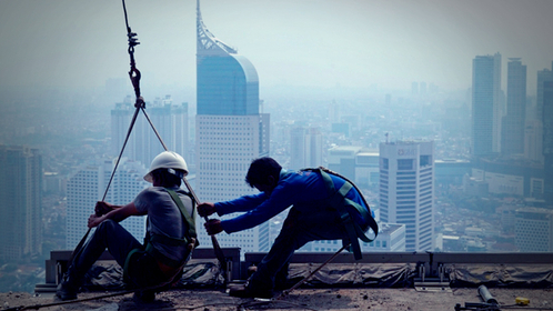 Construction workers labor on a building towering above the business district in Jakarta, Indonesia. MUST CREDIT: Bloomberg photo by Dimas Ardian