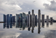 A file photo from 2018 shows ommercial buildings standing reflected in a rooftop pool in Singapore. MUST CREDIT: Bloomberg photo by Brent Lewin.