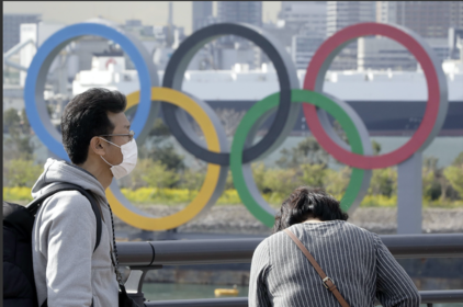 A man wearing a protective mask stands in front of Olympic rings in Tokyo on March 11, 2020. MUST CREDIT: Bloomberg photo by Kiyoshi Ota.