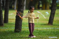 A child plays bubbles at Evergreen Park in Haikou, south China's Hainan province, March 19, 2020. (PU XIAOXU / XINHUA)