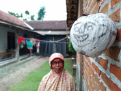 Yasmini, who lives in Wajak Kidul village in Tulungagung, East Java, looks at a 'tetek melek' mask fastened on the outer wall of her home. Some villagers have been placing the masks around their houses to