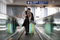 Passengers wearing face masks stand on a moving walkway at Beijing Capital International Airport as the country is hit by an outbreak of the novel coronavirus, March 9, 2020. [Photo/Agencies]