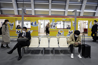 People wearing protective masks sit on a bench on the platform of a subway station in Tokyo on March 26, 2020. MUST CREDIT: Bloomberg photo by Kiyoshi Ota.