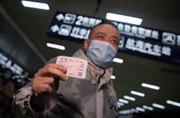 A passenger on train K81 shows his ticket after arriving at Wuchang Railway Station in Wuhan, Central China's Hubei province, on March 28, 2020. Train K81 running from Xi'an to Guangzhou becomes the first passenger train to stop in Wuhan after more than two months of lockdown and transportation suspension in the city. [Photo by Ke Hao/chinadaily.com.cn]