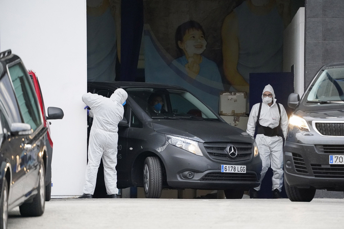 Members of Spain's Military Emergency Unit open a service entrance for a mortuary vehicle to depart at the Palacio de Hielo ice rink, temporarily converted into a morgue for victims of Covid-19, in Madrid, on March 30, 2020. MUST CREDIT: Bloomberg photo by Paul Hanna.