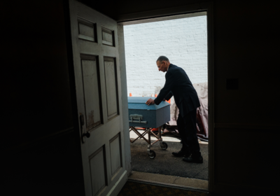 Nick Cassese moves a casket with a man's body inside to a waiting hearse at Gerard J. Neufeld Funeral Home in Elmhurst, N.Y. MUST CREDIT: Photo by Ryan Christopher Jones for The Washington Post
