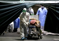 """CASES RISING Health workers on Sunday bring in a new patient, classified as """"under investigation"""" for carrying the coronavirus, at a public hospital in Manila. —RICHARD A. REYES"""
