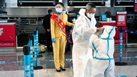 People in white full-body protective suits queueing to check-in at Tianhe International Airport in Wuhan, which reopened to departing passengers yesterday, after being closed for over two months.