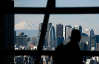 Mount Fuji stands beyond buildings as a visitor looks out at the Tokyo skyline from an observation deck on Jan. 11, 2019. MUST CREDIT: Bloomberg photo by Akio Kon.