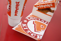 A take-out box and beverage cup are arranged a photograph outside a Popeyes Louisiana Kitchen fast food restaurant in Jeffersonville, Indiana, on Feb. 21, 2017. MUST CREDIT: Bloomberg photo by Luke Sharrett