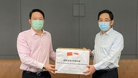 Singapore's Senior Minister of State Lam Pin Min (left) receives a donation of masks from China's ambassador to Singapore Hong Xiaoyong at the Ministry of Health on May 5, 2020.PHOTO: MINISTRY OF HEALTH