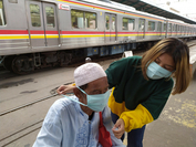A woman helps an old man wear a face mask while he waits for the commuter train at Manggarai Station in South Jakarta on April 5. (JP/P.J. Leo)