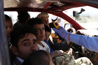 A health worker takes the temperature of people riding a taxi van on May 9, amid concerns about the spread of the coronavirus disease in Sanaa, Yemen. (Khaled Abdullah/Reuters)