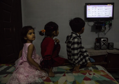 Ahmed (right), 10, with his sister Zari, 8, and cousin Sana, 5, watch English classes on the Pakistan Television network program called teleschool on May 11, 2020. Schools in Pakistan have been closed since March 17 and won't reopen until at least July 15, 2020. MUST CREDIT: Photo by Sarah Caron for The Washington Post.