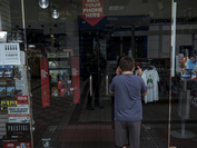 A person looks inside a closed store at a mall in Yuba City, Calif., on May 13, 2020. MUST CREDIT: Bloomberg photo by David Paul Morris.