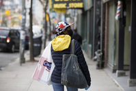 A pedestrian wearing a protective mask carries shopping bags in Toronto on May 19, 2020. MUST CREDIT: Bloomberg photo by Cole Burston.