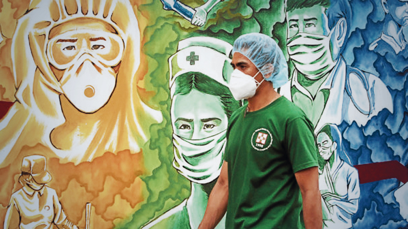 WALL OF FAME A Pasig City hospital worker walks past a mural honoring him and his fellow front-liners in the fight against the coronavirus. —MARIANNE BERMUDEZ