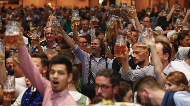 Revelers hold steins of beer aloft at the Oktoberfest in Munich on Sept. 26, 2019. MUST CREDIT: Bloomberg photo by Michaela Handrek-Rehle.