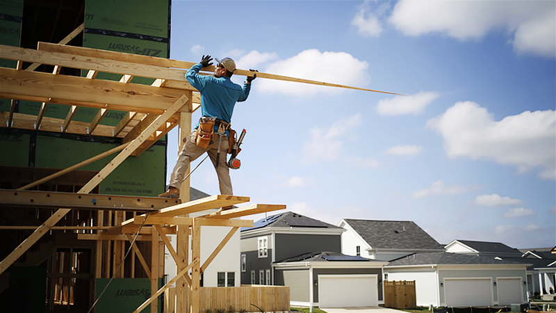 A contractor stands on lumber scaffolding while working on a home under construction in the Norton Commons subdivision in Louisville, Ky.., on March 23, 2020. MUST CREDIT: Bloomberg photo by Luke Sharrett.