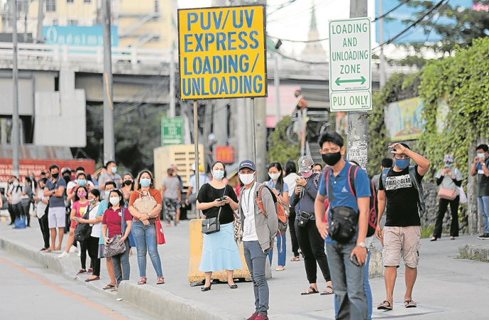THE DAY BEGINS Commuters wait for a ride at a bus stop along Commonwealth Avenue in Tandang Sora, Quezon City, on Monday, when general community quarantine took effect. But public utility vehicles were mostly out of sight, as workers venturing to return to their jobs found out. —GRIG C. MONTEGRANDE