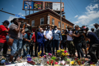 Terrence Floyd, the brother of George Floyd, center in white T-shirt, visits a memorial for his brother at the intersection of 38th Street and Chicago Avenue in Minneapolis on Monday. MUST CREDIT: Washington Post photo by Salwan Georges.