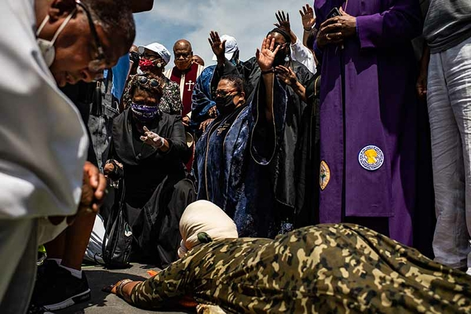 Twin Cities clergy members pray Tuesday at a memorial for George Floyd in Minneapolis. As unrest tied to Floyd's killing while in police custody has spread to other parts of the country, including Washington, a relative calm has emerged in Minneapolis, even as protests continue.