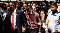 George Floyd's son, Quincy Mason Floyd, center, holds hands with his family's lawyer, Benjamin Crump, on Wednesday as they visit the site where his father was killed by a Minneapolis police officer. MUST CREDIT: Washington Post photo by Salwan Georges