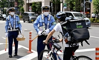 An Uber Eats delivery rider is stopped by a police officer in Nakano Ward, Tokyo, on Friday.