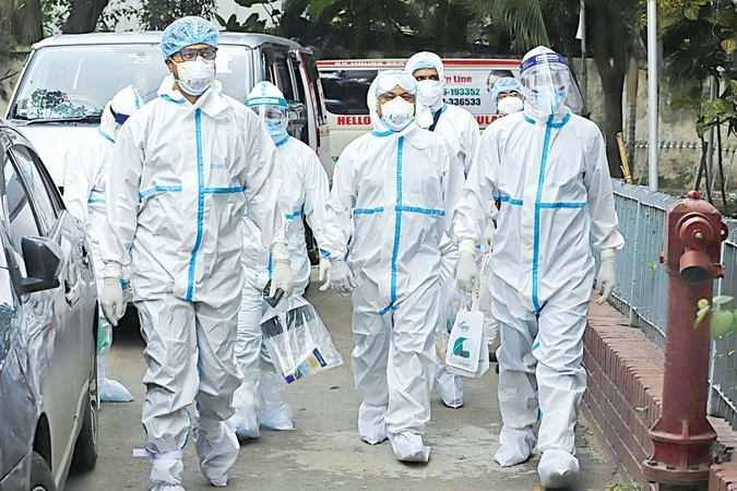 Doctors clad in PPEs enter the Covid-19 unit at Dhaka Medical College Hospital. Despite fears of infection, they have been treating patients for around two months, staying at a city hospital far from home. The photo was taken recently. Photo: Amran Hossain