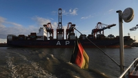 The German national flag flies from a sightseeing boat near conatainer ship 'APL Detroit' at the Port of Hamburg in Hamburg, Germany, on June 7, 2020. MUST CREDIT: Bloomberg photo by Krisztian Bocsi.