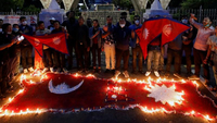 Nepalese people light candles as they celebrate after the Parliament approved a new map of the country, including areas disputed with India, in Kathmandu, Nepal [Navesh Chitrakar/Reuters]