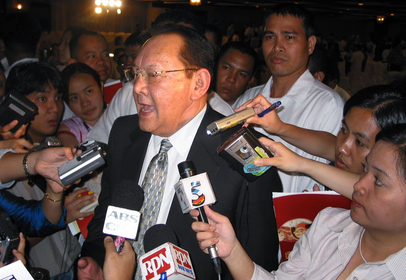 Eduardo Cojuangco speaks to reporters after being re-elected as chairman of San Miguel, the Philippines' largest food and beverage business empirem in Manila on April 20, 2004. MUST CREDIT: Bloomberg photo by Jose Reinares