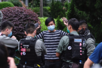 Police officers stop and search a demonstrator in Hong Kong on June 9, 2020. MUST CREDIT: Bloomberg photo by Roy Liu