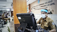 South Tangerang Civil Registration Office staff wear protective gear as they serve citizens in Cilenggang, South Tangerang, Banten, on Tuesday, a day after the office was reopened. (JP/Seto Wardhana)