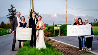 The families of Matt and Liz Peters stand at the U.S.-Canada border to celebrate the couple's marriage. MUST CREDIT: Photo courtesy of Ron Peters Photography Photo by: Photo courtesy of Ron Peters Photography — Photo courtesy of Ron Peters Photography