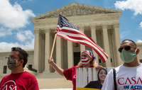 Ivania Castillo, a board member of CASA in Action in Prince William County (Virginia), waves a flag outside the Supreme Court building in Washington on Thursday, the day the court rejected the Trump administration's attempt to dismantle the program protecting undocumented immigrants brought to the country as children. MUST CREDIT: Washington Post photo by Jonathan Newton